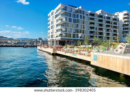 OSLO, NORWAY - AUGUST 13: Environment in modern district with sunbathing young people on man-made beach in warm day on August 13, 2015 in Oslo, Norway #398302405