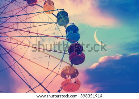 Vintage photo with ferris wheel against the moon colorful sky  #398351914