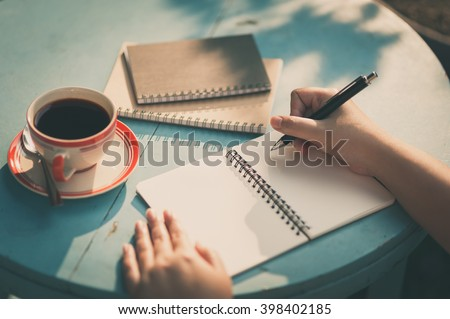 Woman right hand writing journal on small notebook at outdoor area in cafe with morning scene and vintage filter effect Royalty-Free Stock Photo #398402185