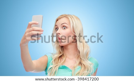 expressions, technology and people concept - funny young woman or teenage girl taking selfie with smartphone and making fish face over blue background