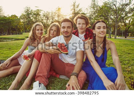 Big company of young people sitting on the grass in the park #398482795