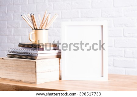 Desk with blank white picture frame and pencils in iron mug placed on books and wooden box. Mock up