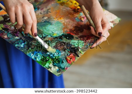 artists brushes and oil paints on wooden palette. macro artist's palette, texture mixed oil paints in different colors and saturation. palette with paintbrush and palette-knife hands.  #398523442