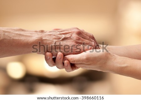 Female hands touching old male hand - taking care of the elderly concept #398660116