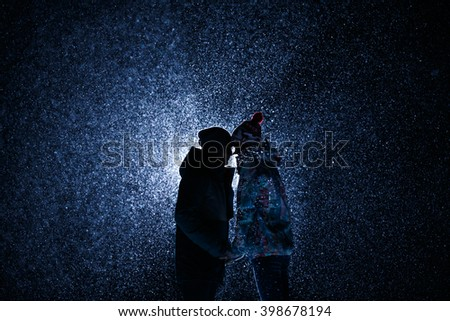 silhouette Man and girl at night under the snow. met today embrace and kiss. Suitable for sport theme, snowboards or skis. A lot of snow #398678194