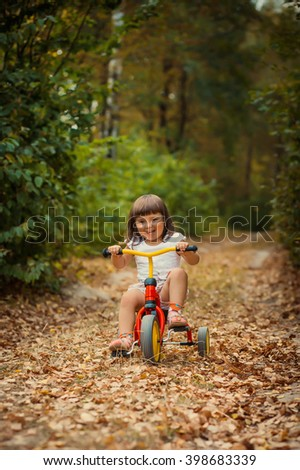 Adorable girl riding a bike in the forest. beautiful autumn day #398683339