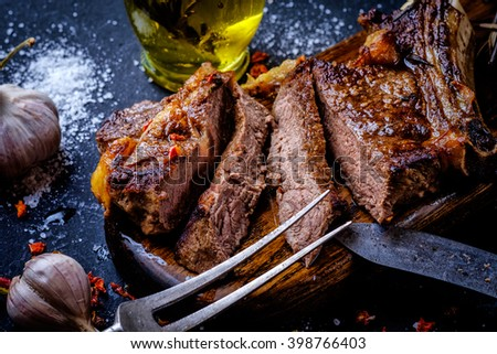 Grilled steak sliced on a cutting board. Entrecote with garlic and chilli on a dark background. #398766403