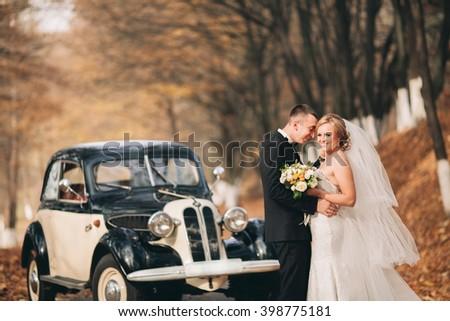 Stylish wedding couple, bride, groom kissing and hugging near retro car in autumn #398775181
