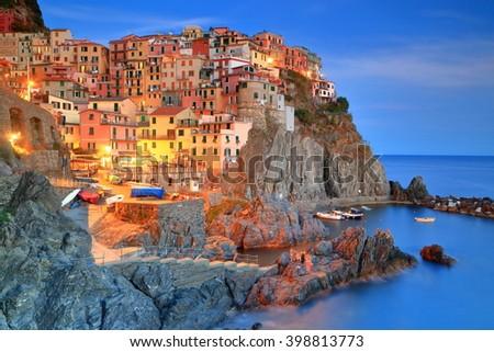 Evening lights illuminate historical village Manarola, Cinque Terre, Italy #398813773