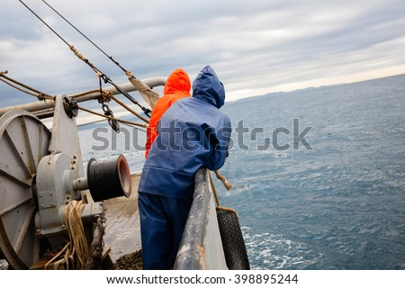 Fishermen in waterproof suits on the deck of the fishing vessel. Morning time. #398895244