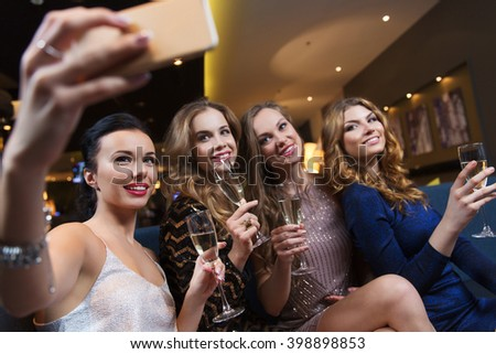 celebration, friends, bachelorette party, technology and holidays concept - happy women with champagne glasses and smartphone taking selfie at night club