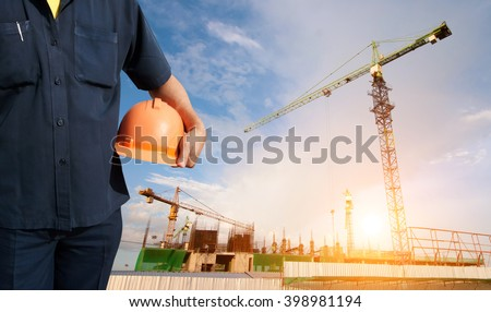 engineer holding orange helmet on background of new office buildings and construction cranes in blue sky - Sunlight filter effect #398981194