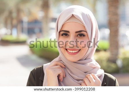Smiling girl in hijab covering her eyes with happiness in Dubai Marina #399012208