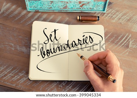 Retro effect and toned image of a woman hand writing a note with a fountain pen on a notebook. Handwritten text Set Boundaries as success and evolution concept image Royalty-Free Stock Photo #399045334