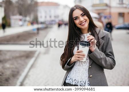 Beautiful business woman drinks coffee on a street #399094681