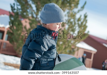 Little boy with grey toboggan carrying a sled looking down. #399163507