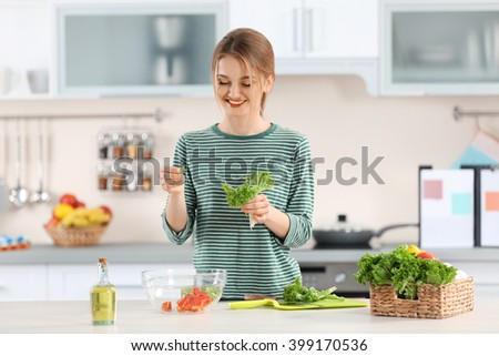 Young woman preparing vegetable salad in the kitchen #399170536
