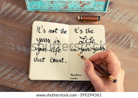 Retro effect and toned image of a woman hand writing on a notebook. Handwritten quote It's not the years in your life that count. It's the life in your years - Abraham Lincoln as concept image #399294361