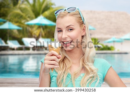 summer vacation, travel, tourism, junk food and people concept - young woman or teenage girl in sunglasses eating ice cream over pool on resort beach background #399430258