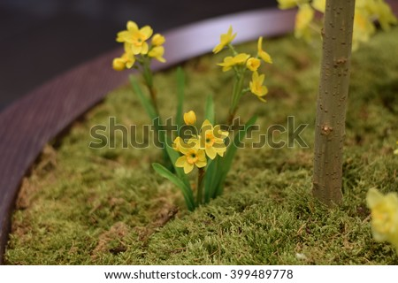 Easter holiday decorations involving yellow bird flowers, colored Easter eggs on the wooden branches and narciss flowers on the green grass field #399489778