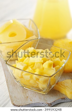 Sliced fresh pineapple in glass saucers on wooden table closeup #399593248