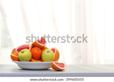 Plate of ripe fruits on a table #399600505