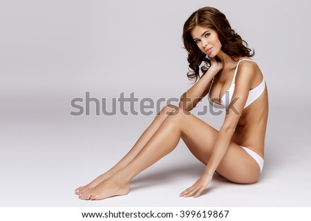 Slim tanned woman's body over gray background #399619867