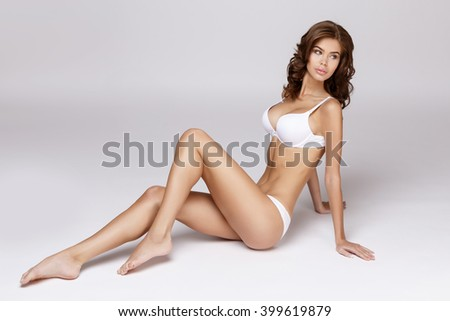 Slim tanned woman's body over gray background #399619879
