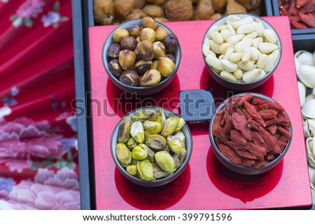 Top view on serving cups filled with variety of nuts and seeds on snacks bar.  Oriental design red background. #399791596