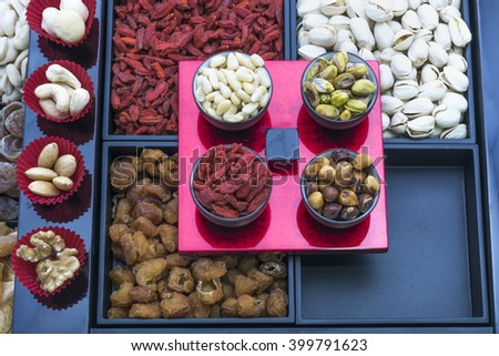 Top view on multi-tier trays and serving cups filled with variety of nuts and sweetened fruits on snacks bar.   #399791623
