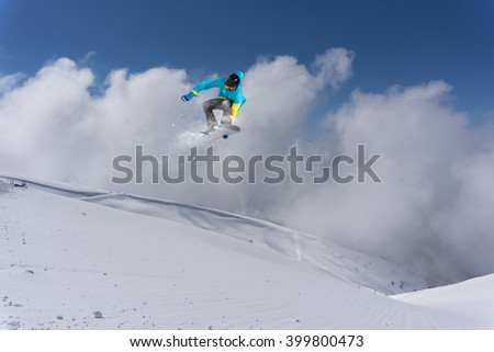 Snowboarder jumping on mountains. Extreme sport. #399800473