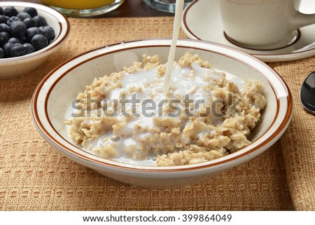 Milk being poured on a bowl of oatmeal #399864049