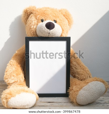 Vintage blank picture frame and teddy Bear sunlight on a wall.
