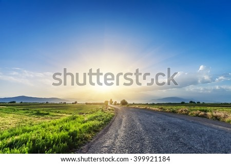magnificent landscape of road on meadow on background of beautiful sunset sky with clouds #399921184