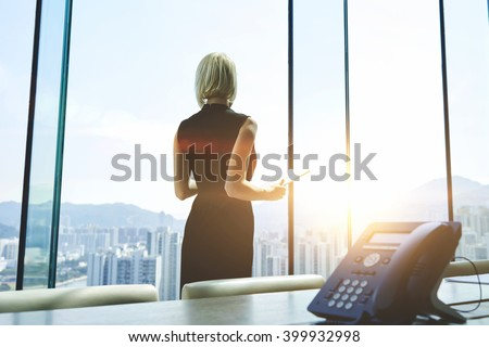 Back view of a businesswoman with digital tablet in hands is watching in office window on a New York city view and thinking about future her company. Female manager is using touch pad during work day #399932998