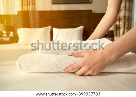 Close-up of hands putting stack of fresh white bath towels on the bed sheet. Room service maid cleaning hotel room. Lens flair in sunlight #399937783