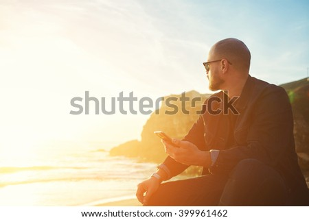 Young hipster man traveler with cell telephone in hand is enjoying amazing landscape, while is sitting on the beach near ocean with copy space background for your text message or advertising content #399961462