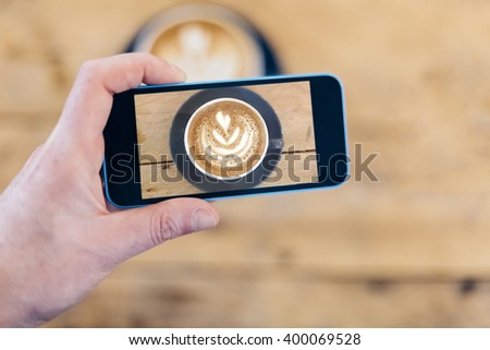 Hand Taking Picture with a Smart Phone of His Cappuccino