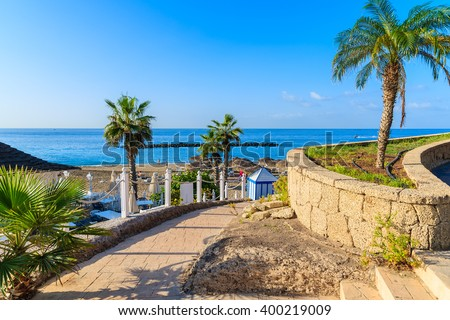 Walkway with palm trees to exotic El Duque beach in Costa Adeje town, Tenerife, Canary Islands, Spain Royalty-Free Stock Photo #400219009