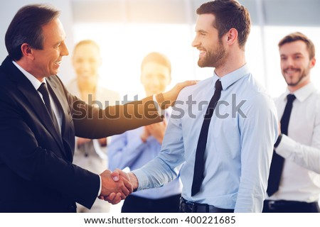Great job! Two cheerful business men shaking hands while their colleagues applauding and smiling in the background #400221685