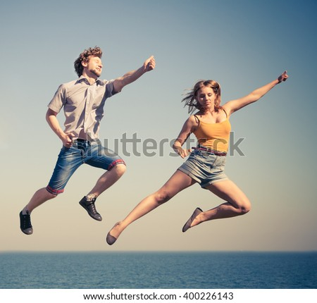 Carefree young couple friends jumping by sea ocean water. Happy woman and man having fun. Summer happiness and freedom. #400226143