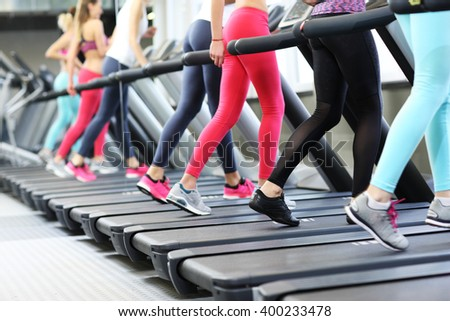 Group of fit women working out on treadmill in gym #400233478