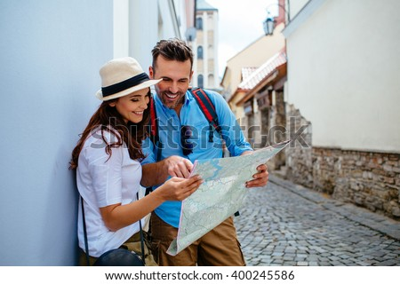 Happy couple on vacation sightseeing city with map Royalty-Free Stock Photo #400245586