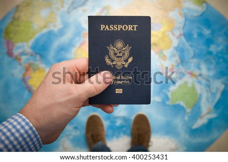 Man's hand holding US passport. Map background. Ready for traveling. Open world. #400253431