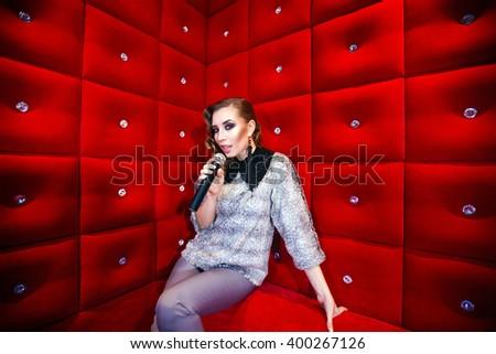 beautiful girl singing karaoke in a nightclub #400267126