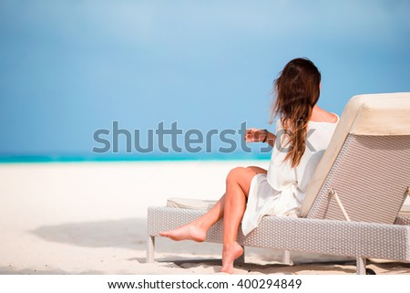 Young woman on lounger with mobile phone at the beach #400294849
