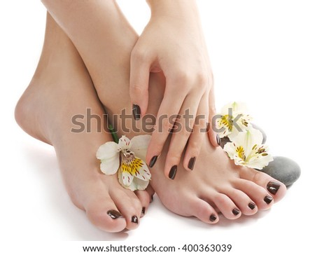 Manicured female feet and hand with spa stones and flowers isolated on white #400363039