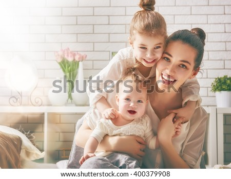 Happy loving family. Mother and her daughters children girls playing and hugging. Royalty-Free Stock Photo #400379908