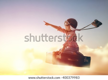 Dreams of travel! Child flying on a suitcase against the backdrop of a sunset. Royalty-Free Stock Photo #400379983