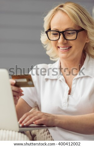 Beautiful old woman in casual clothes is holding a credit card, using a laptop and smiling while sitting in armchair at home #400412002